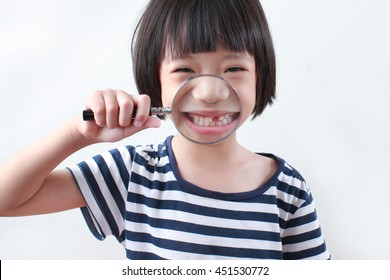 Cute asian girl with magnifier showing her first lost tooth