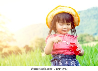Cute Asian girl, in the meadow, blowing bubbles.