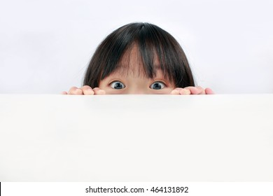 A cute Asian girl peaking over a table's edge