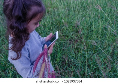 Cute Asian girl is playing on the grass phone.
