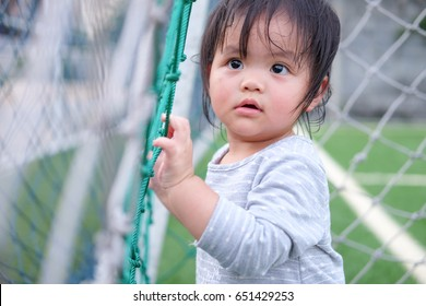 Cute asian girl playing on football field. Portrait of Asian beautiful baby girl of 1 year and 3 months old.