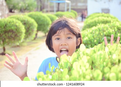 Cute Asian girl playing peekaboo at park , childhood concept.