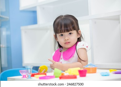Cute Asian girl playing toys happily.