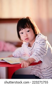 Cute Asian girl reading a book with nature rim light.