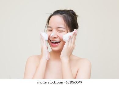 cute Asian girl scrub facial cleansing foam on her face for good health skin