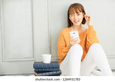 Cute Asian girl, short hair, wearing orange knitwear And white pants , Happy listening to music,have books and coffee piles