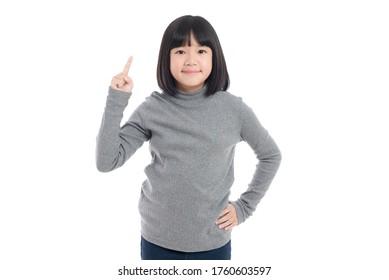 Cute asiatisches Mädchen, das mit der ersten Fingernummer auf weißem Hintergrund einzeln zeigt und zeigt