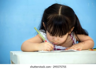 Cute Asian girl sitting happily drawing, coloring.