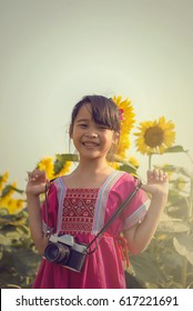 A cute Asian girl taking a photo in the sunflower field.