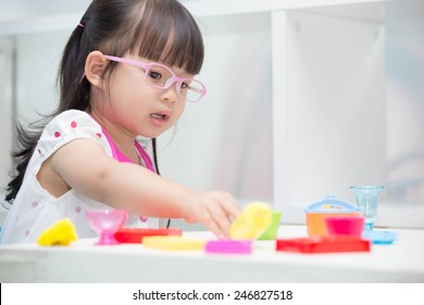 Cute Asian girl wearing glasses playing toys happily.