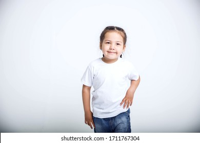 Cute Asian girl in white t-shirt and jeans standing on white background isolated