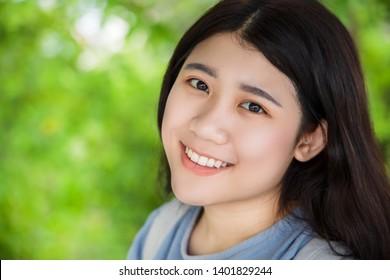 cute Asian healthy plump teen girl smile wth beautiful blur green nature background