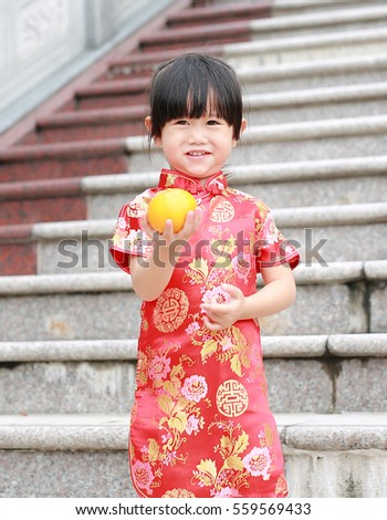 606b19e7ef072 Cute asian kid girl in Red Traditional Chinese dress with holding sacred  Orange at chinese temple