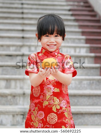 a63c65ee5d5e3 Cute asian kid girl in Traditional Chinese dress with holding sacred Orange  at chinese temple in