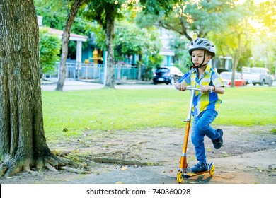 Cute Asian kid learning to ride scooter in a playground park on summer day. Preschooler boy wear safety helmet. Boy riding roller. Asian Kid play outdoors with scooters. Active outdoor sport for child