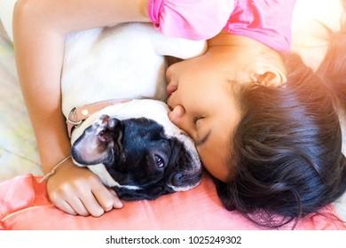 cute asian kid teen girl sleep lay hug awake french bulldog puppy dog on bed in orange morning light