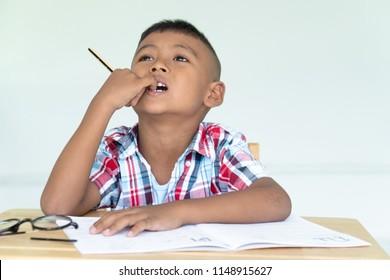 Cute asian little boy write homework