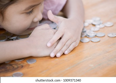 Cute asian little child girl hugging and stingy her money. Kid saving money for the future concept