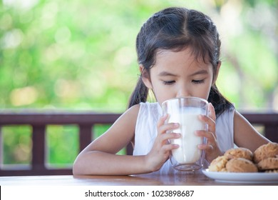 Cute asian little child girl is drinking a milk from glass with cookies for breakfast