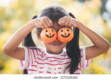 Cute asian little child girl with bucket pumpkin. Funny kid for Halloween celebration.