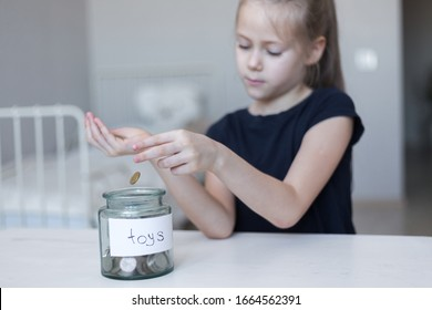 Cute asian little child girl putting coin into glass bottle in the garden. Kid saving money for the future concept