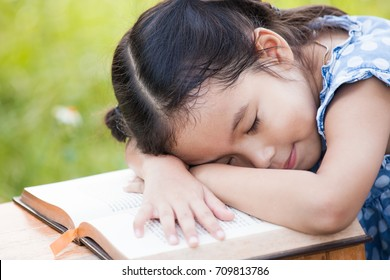 Cute asian little child girl is sleeping and lie down on a book