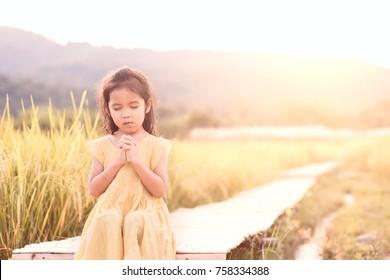 Cute asian little child girl praying with folded her hand and sitting on bamboo walkway in the paddy field in vintage color tone