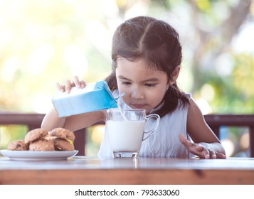 Cute asian little child girl pouring milk into glass for breakfast
