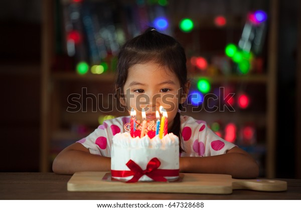 Cute asian little girl with birthday cake in birthday party in dark tone