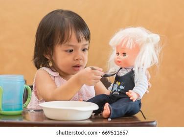Cute asian little girl feeding a doll.