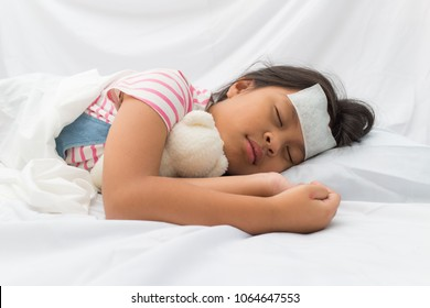 Cute asian little girl with fever reducer stick forehead and sleeping hug bear doll in the bed,