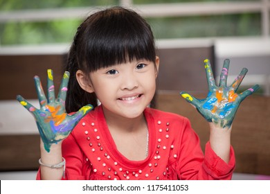Cute asian little girl with hands in paint , in classroom school  concept - happy children showing painted hand palms at preschool . Early education . kid in kindergarten . intelligence