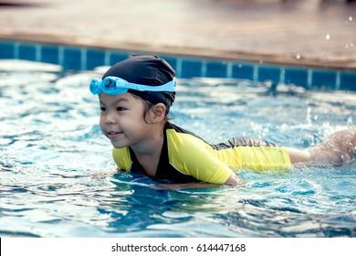 Cute asian little girl having fun to swim in swimming pool