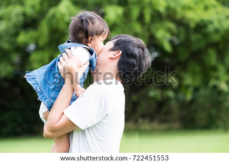 bee6310b5 Cute asian little girl is kissing her father cheek during the playing time  in the park