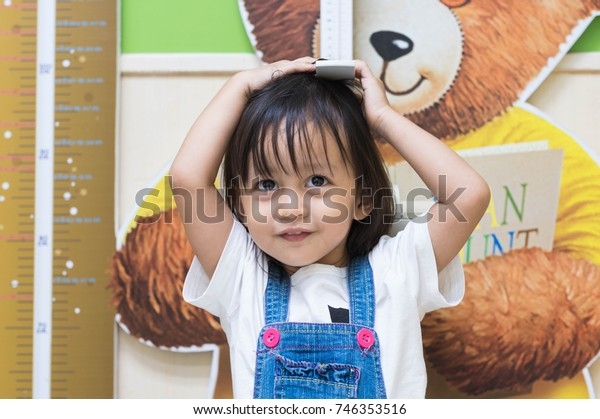 Cute asian little girl is measuring body height herself at the hospital before vaccination, concept of healthy kid.