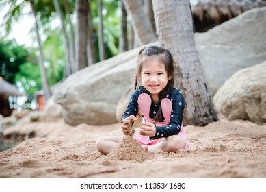 Cute asian little girl playing with sand.