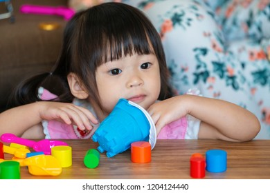 Cute asian little girl playing and learning different shape with a toy.