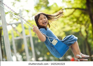 Cute Asian little girl playing on a swing and having fun in park