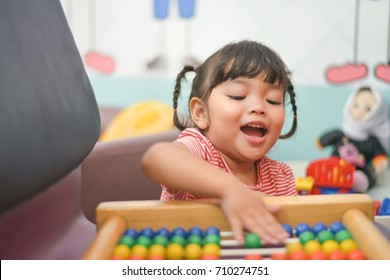 Cute Asian little girl playing with abacus at home. Smart child learning to count. learning,classroom,lesson concept.