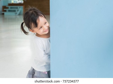 Cute asian little girl is playing hide and seek with funny moment, concept of learning by playing for child development.
