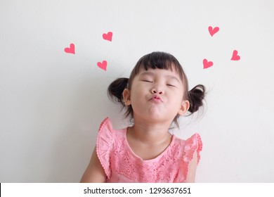 Cute Asian little girl sending kiss with drawing hearts. Isolated white background.