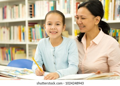 Cute Asian little girl sitting at the desk with her loving mother doing homework smiling to the camer happily copyspace education positivity family love support studying learning childhood parenting.