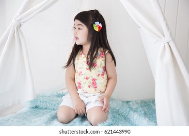 Cute Asian little girl sitting down on the blue carpet floor inside the vintage tent while she looking to something