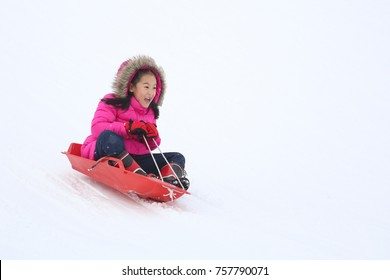 Cute Asian little girl sliding down from the hill top covered with white and fluffy snow in one of ski area in Japan. One of the children favorite activity in winter time.