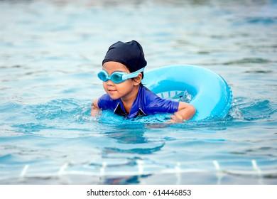 Cute asian little girl with swim ring is having fun to swim in swimming pool
