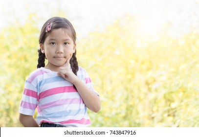 cute asian little girl thinking on yellow flower background
