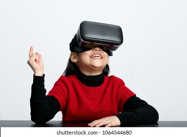 Cute Asian little girl wearing vr glasses interacting, studio shot