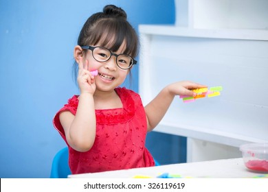 Cute Asian little girl  Wearing a red shirt and glasses playing toys happily.