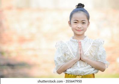 Cute asian little girl wearing thai dress pay respect