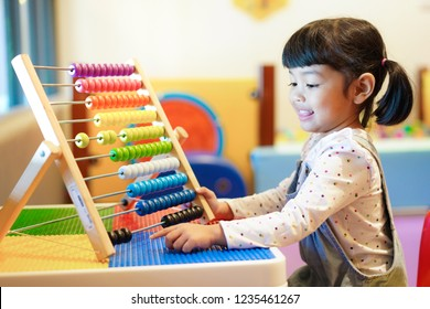 Cute Asian little kid girl playing with abacus at home. Smart child learning to count. learning, classroom, lesson concept.